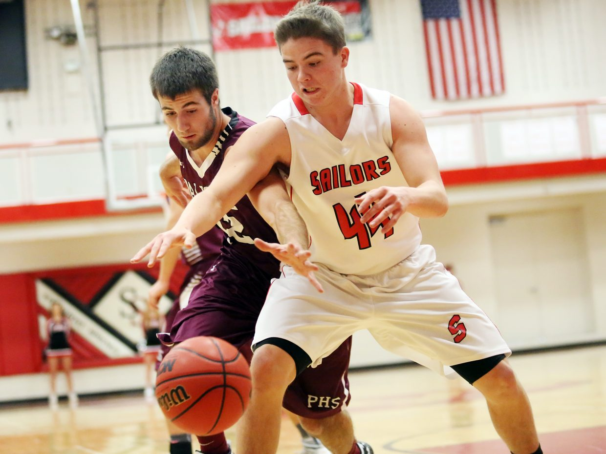Steamboat Springs junior Charlie Harrington, right, fights for a loose ball with Palisade's John Goff on Saturday inside the Kelly Meek gymnasium. The Sailors lost, 60-50.