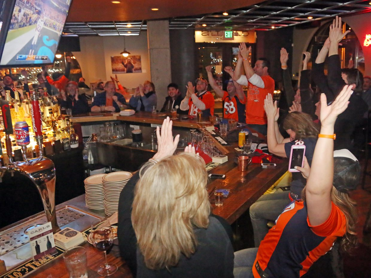 Denver Broncos fans celebrate while watching the Super Bowl at Carl's Tavern in Steamboat Springs Sunday night. The Broncos defeated the Carolina Panthers 24-10.