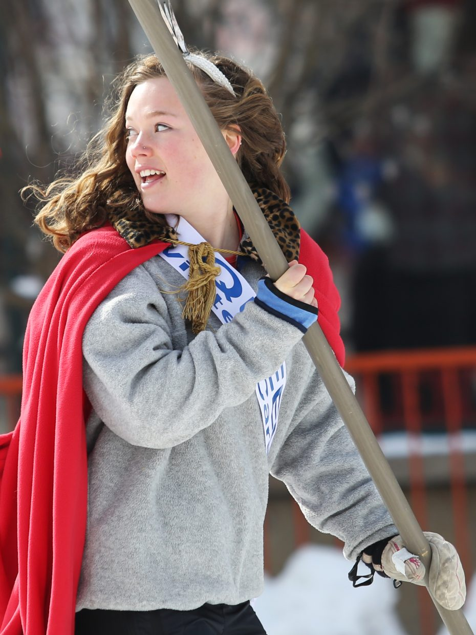 Winter Carnival Queen Logan Sankey, carrying the American flag, glances back during the Diamond Hitch Parade on Sunday.