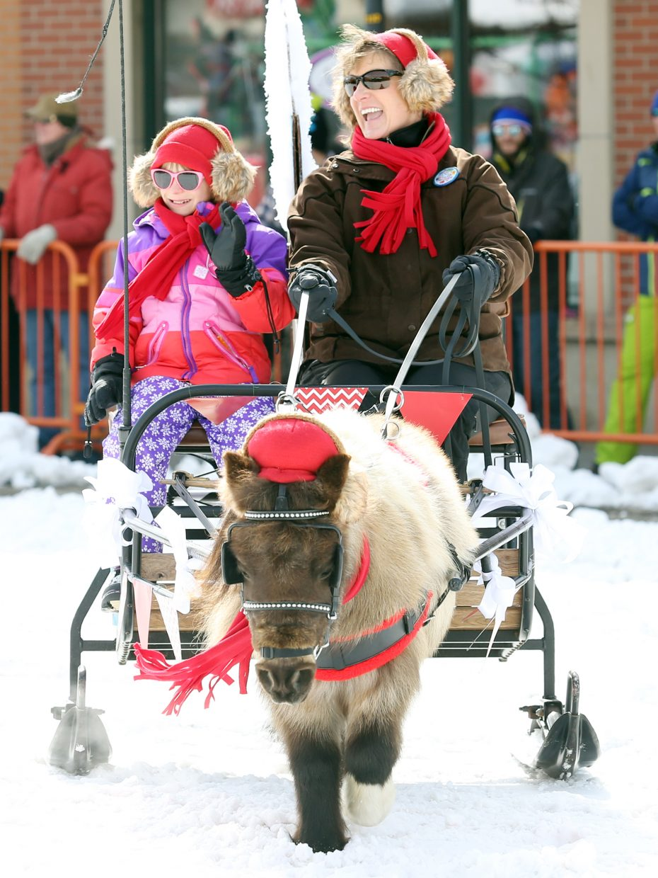 Led by Squirt, Ann Kvols and her daughter, Alley, of the Circle K Ranch, take part in Sunday's Diamond Hitch Parade in downtown Steamboat Springs.