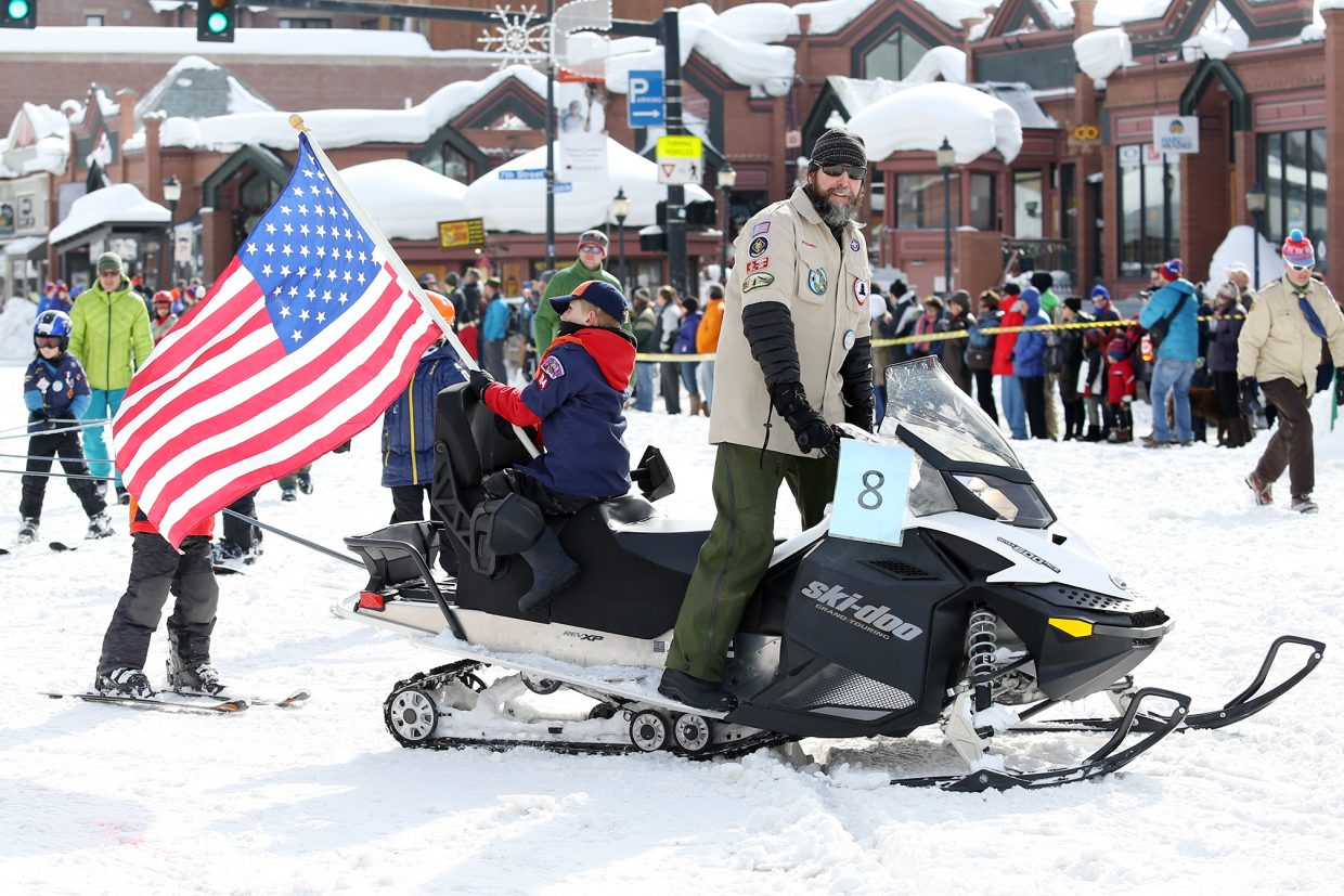 Members of Cub Scouts Pack 194 are led down Lincoln Avenue by snowmobile Sunday during the Diamond Hitch Parade.