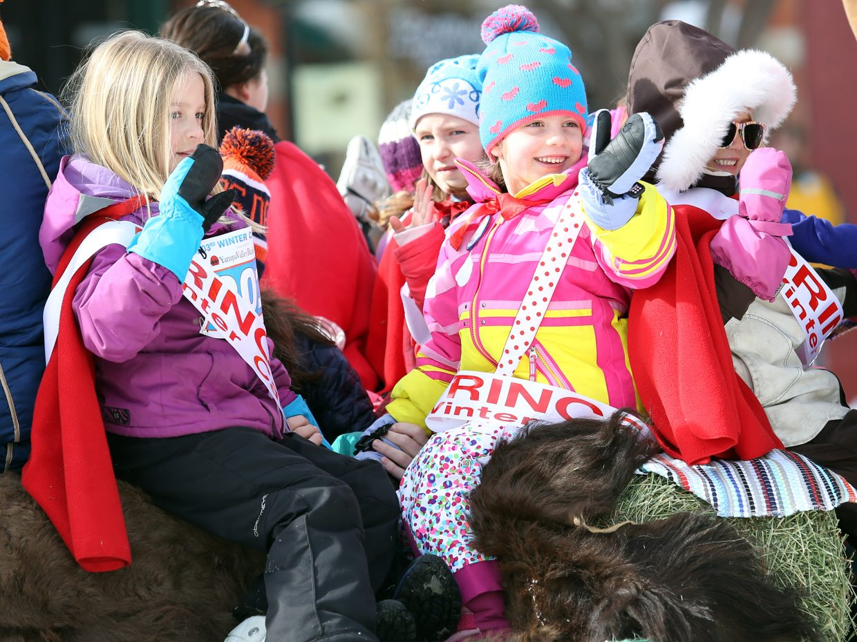 Young members of the Ladies Recreation Club wave at spectators during Sunday's Diamond Hitch Parade in downtown Steamboat Springs.