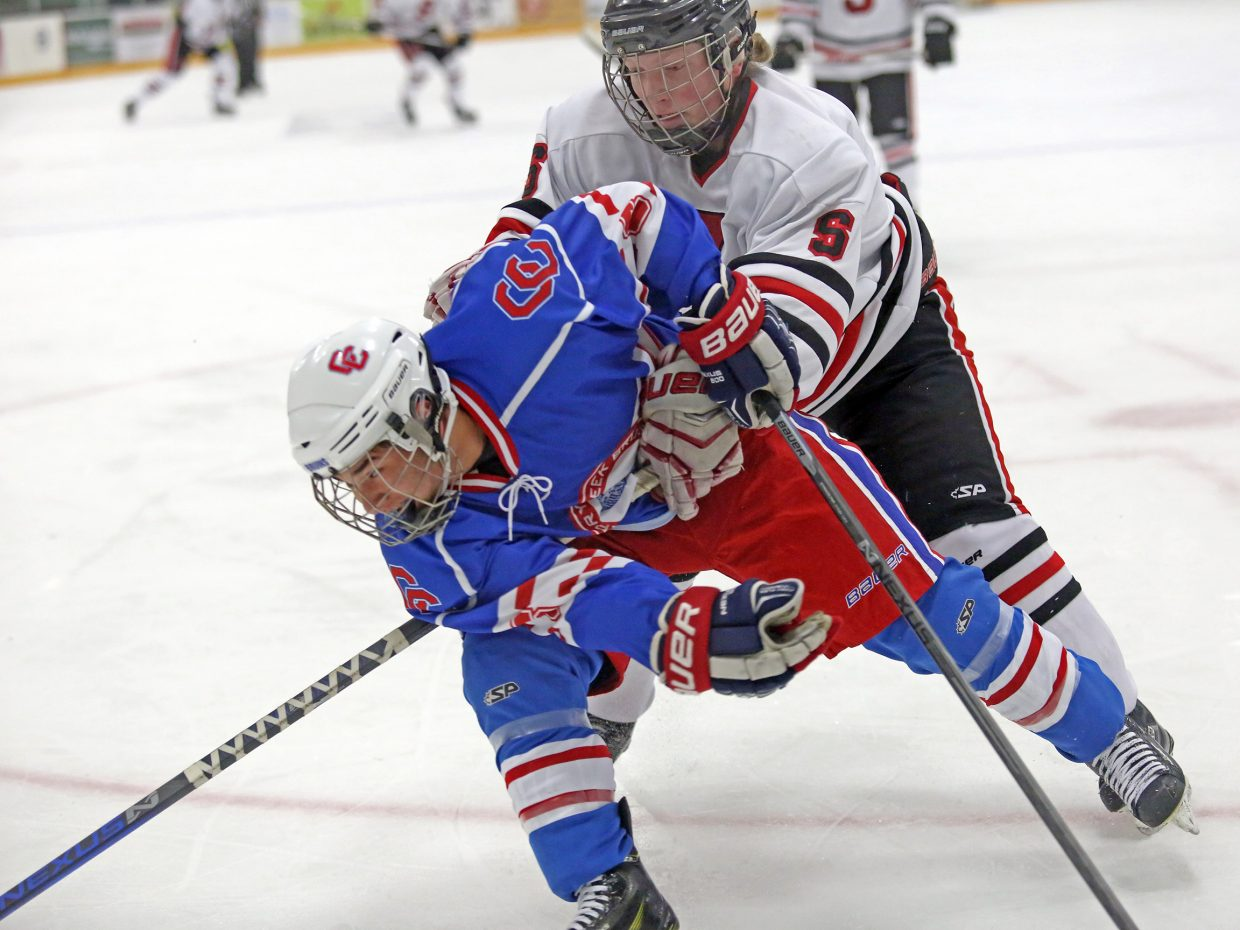 Steamboat Springs senior David Cropper, back, gets physical with a Cherry Creek defender on Saturday at Howelsen Ice Arena. The Bruins won, 5-2.
