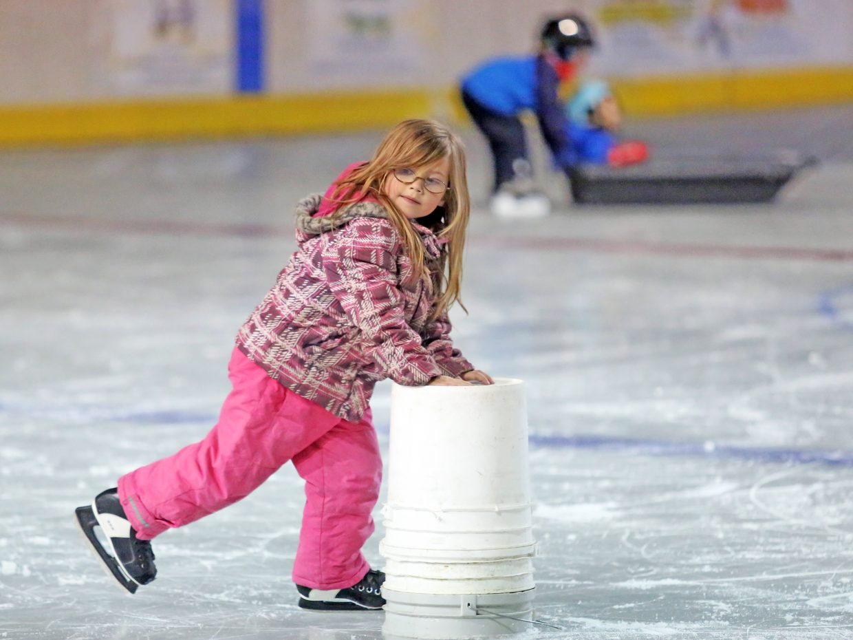 Ella Rae Hood, 5, uses a bucket to help her scoot around on the ice Friday during Oak Creek's WinterFest event at the Oak Creek Ice Rink. Music, food and lots of ice skating were the main draws to the winter celebration.