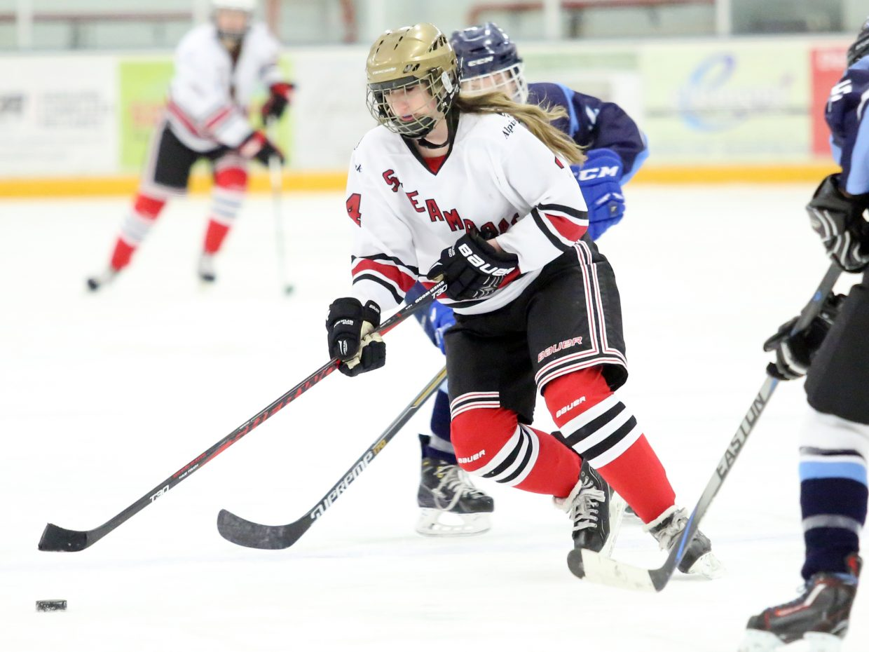 Steamboat Springs U19 hockey player Jacquelyn Brown goes between two Colorado Select defenders on an offensive attack Sunday in the team's regular-season finale at Howelsen Ice Arena.