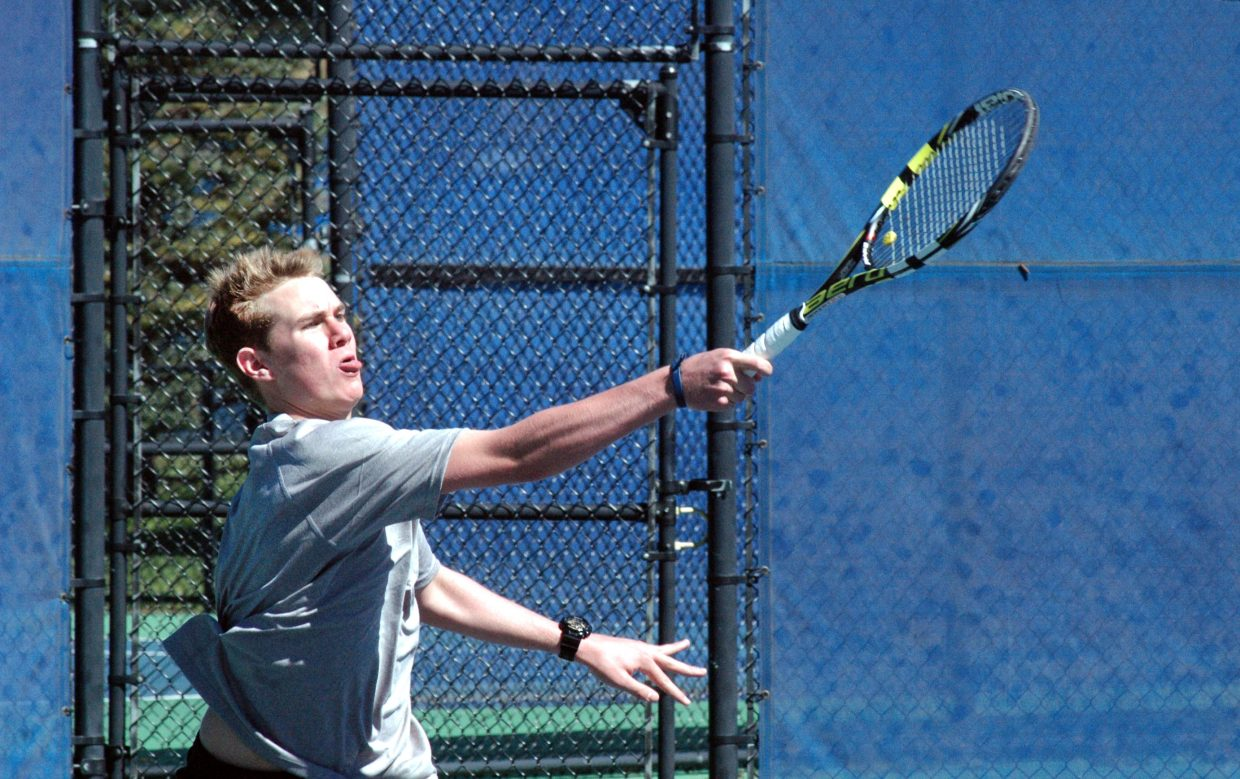 Steamboat's Nick Sear drives in a shot in the No. 4 doubles match Saturday. Sear and partner Peter Wharton were challenged against Evergreen but pulled out a three-set victory.