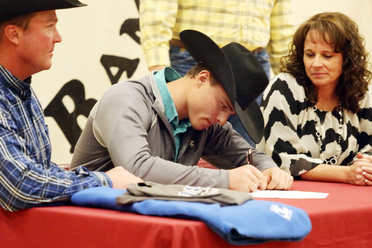 Soroco High School senior Eric Logan, center, is surrounded by his father Mark Logan and mother Jeannie Jo Logan, as he signs his letter of intent Thursday in Oak Creek to join the rodeo program at Odessa College in Texas next year.