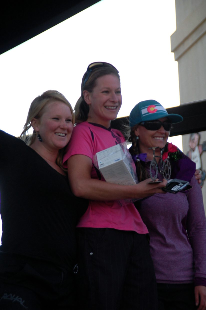 Women's elite class winner Liana Gregory, center, accepts her first-place award alongside Sarah Dills, left, and last year's Quick and Chainless winner Alana Ratzell.
