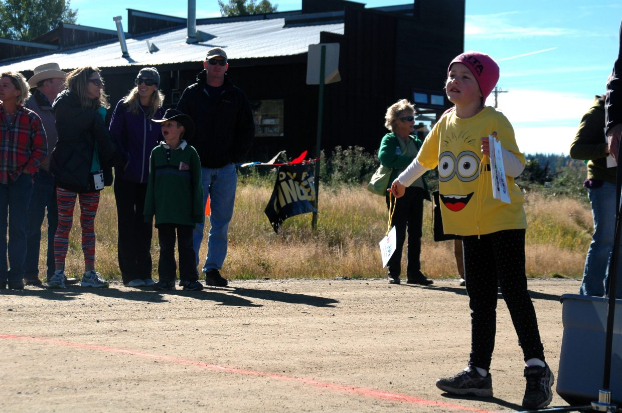 Ellie Reynolds, 6, waits with a ribbon for her twin sister, Eva, at the finish line of the 1-mile fun run at the Wildflower Loop Race in Hahn's Peak Village.