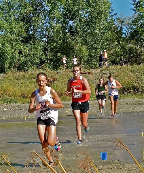 Steamboat Springs High School senior cross-country runner Meg O'Connell dashes across some water during the Rampart Foxes and Hounds Invitational last weekend. The team is hosting its first-ever community wide homecoming race this Friday night.