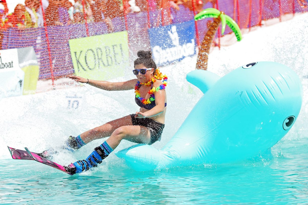 """Ashley Spiegel, or """"Beach Babe,"""" bounces off the inflatable whale Sunday during her run at the Splashdown Pond Skim at Steamboat Ski Area. The event was part of Springalicious 2016 and celebrated the ski area's seasonal closing."""