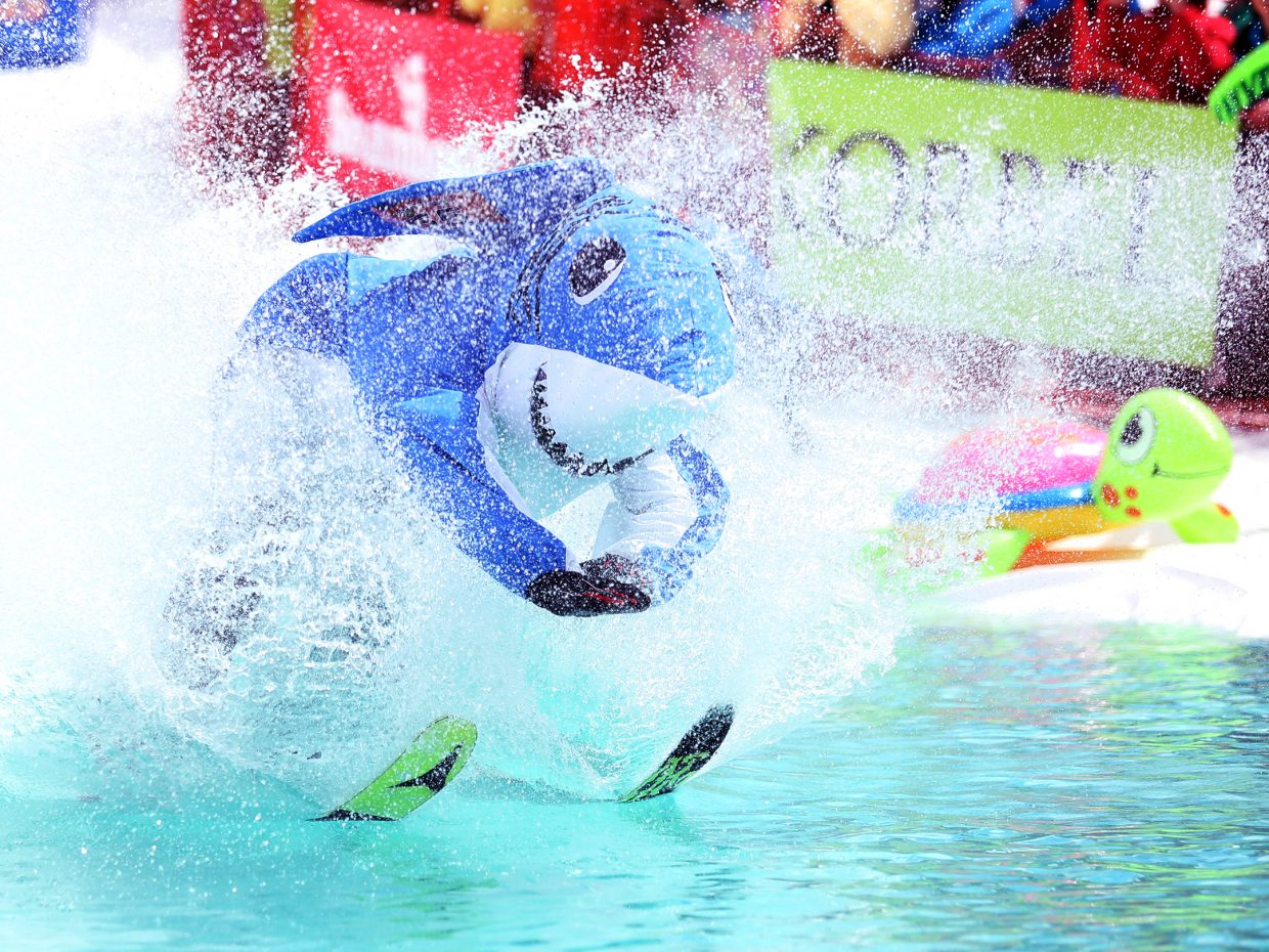 """Brooks Hinkle, dressed as """"Dancing Snow Shark,"""" plows through the water during the 2016 Splashdown Pond Skim at Steamboat Ski Area. The event was cancelled this year due to unseasonably warm conditions."""