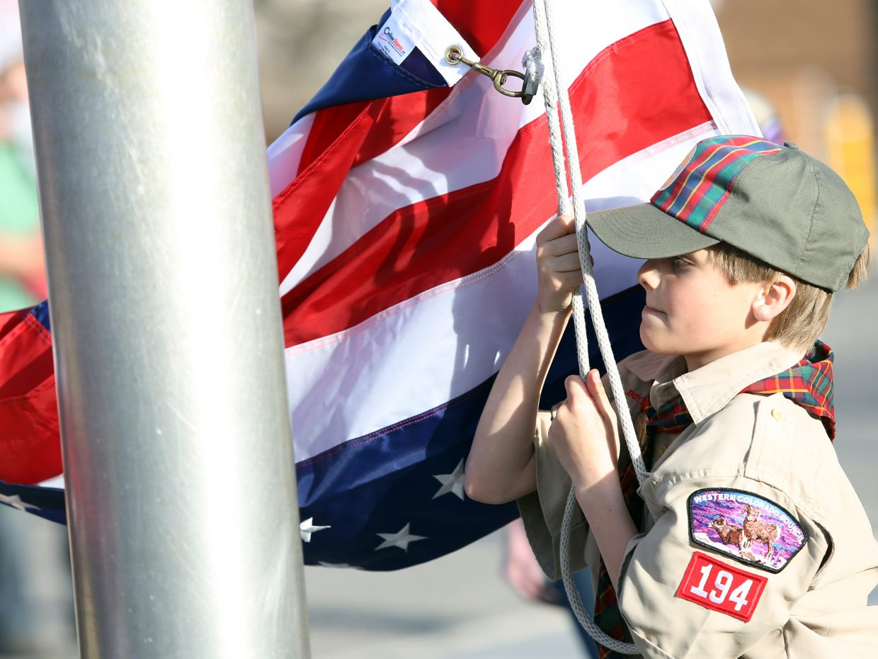 Steamboat Springs Cub Scout Pack 194's Thomas Mauldin begins to raise the American flag Wednesday outside the middle school. The formal flag ceremony was held, in part, as a community service project to replace the older, worn flag, but also served as a chance for the scouts to earn an achievement related to the handling of the flag.