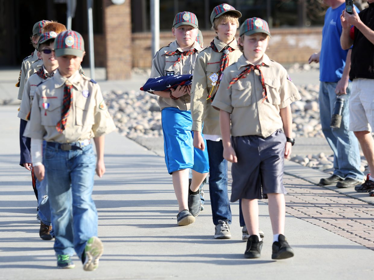 Steamboat Springs Cub Scout Pack 194 members begin to march toward the flag pole outside of the middle school Wednesday, the start of the formal flag ceremony.