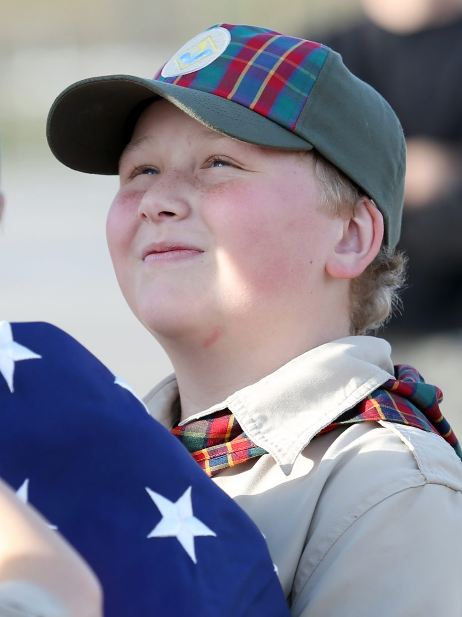 Steamboat Springs Cub Scout Pack 194's Jackson Riley helps keep the American flag off the ground while it is raised during Wednesday's ceremony.