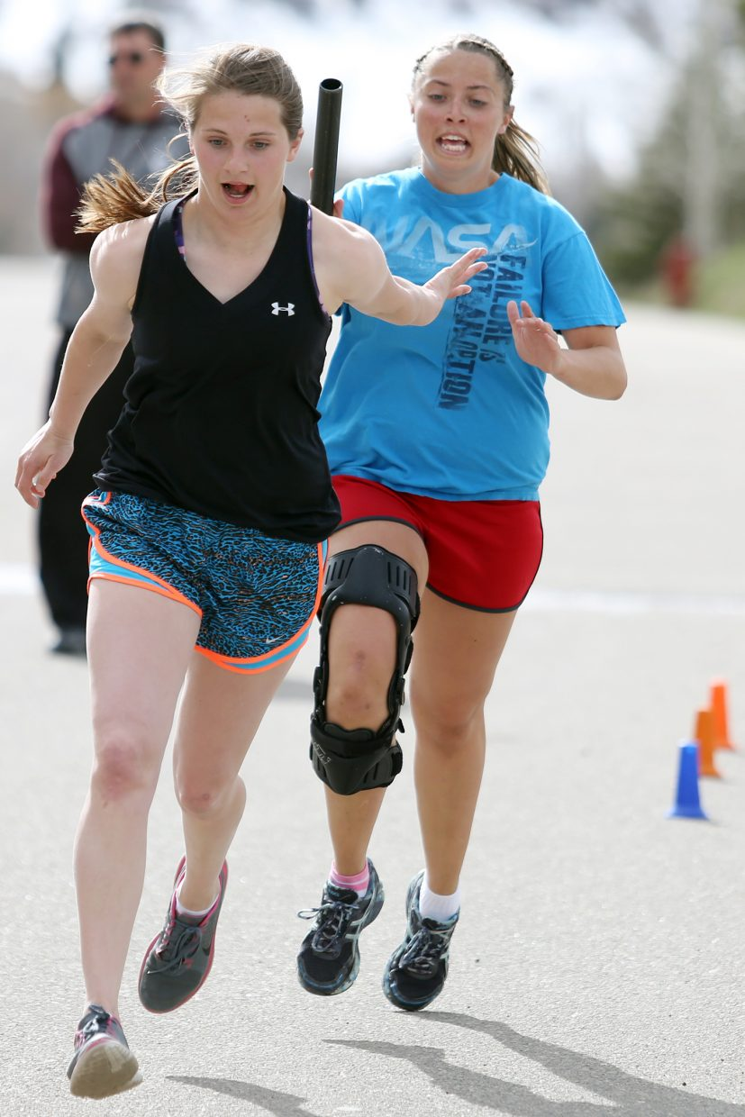 Soroco High School sophomore Mattie Rossi, left, and junior DaKota Bruner practice relay handoffs outside the school Thursday in Oak Creek.