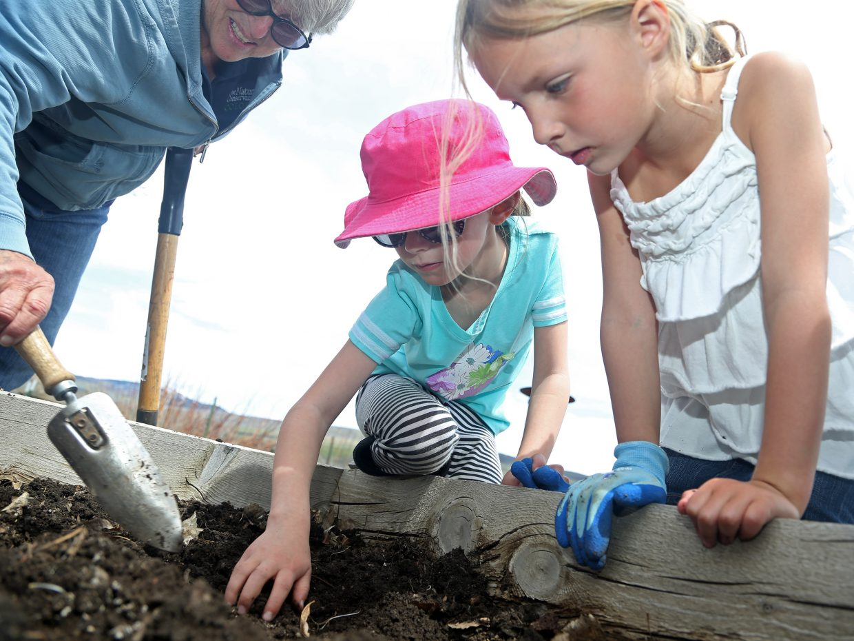 Elementary school students Molly Grady, right, and Allison Reznicek, center, dig for worms with the help of The Nature Conservancy's Betsy Blakeslee Friday at Carpenter Ranch near Hayden. More than a dozen students took part in the City of Steamboat Springs School Days Off program's 10th annual trip to the ranch for Earth Day.