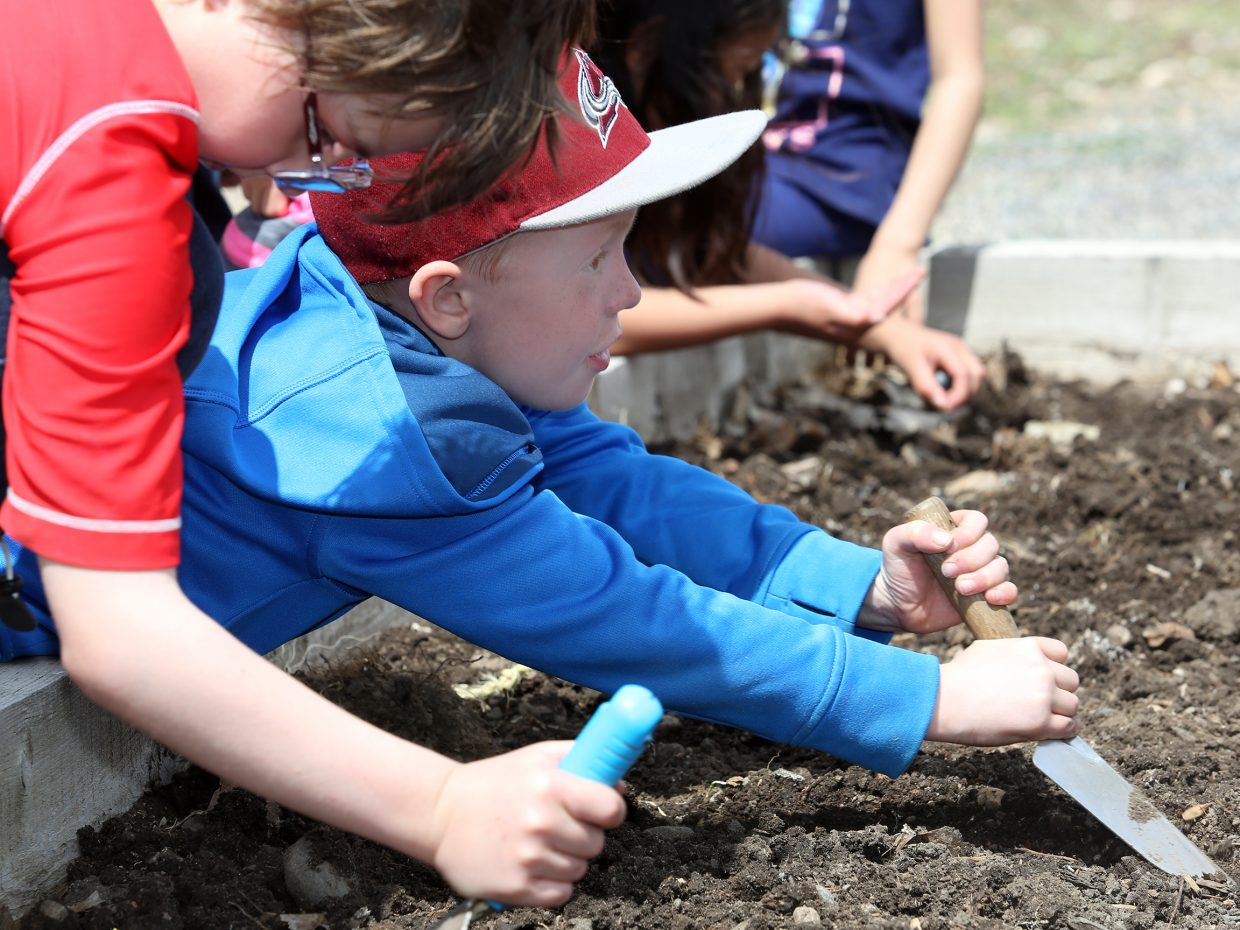 Parker Horne makes a spot to plant his vegetable seeds Friday at Carpenter Ranch.