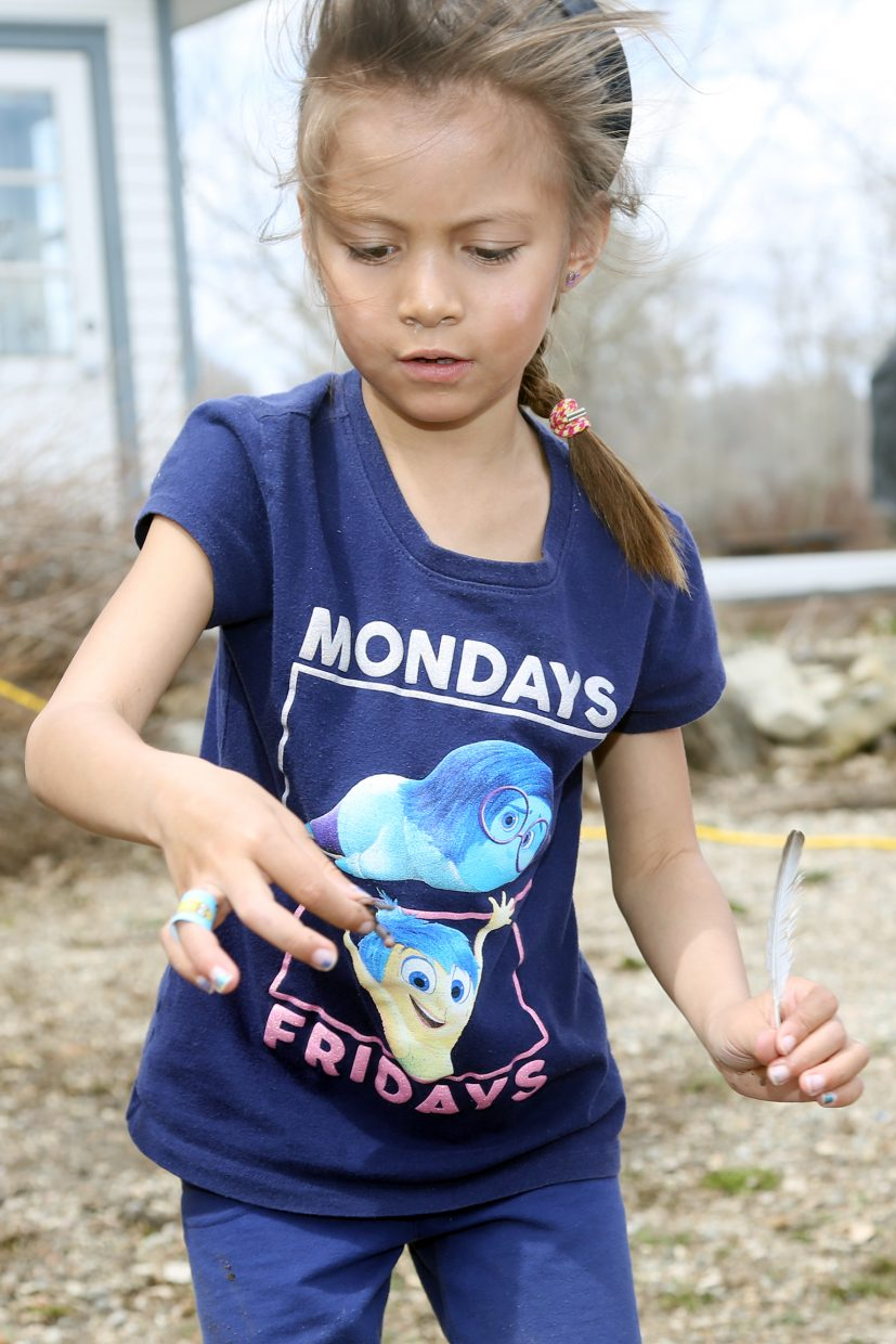 """Callie Mappala takes the worm she found to the """"work bucket"""" Friday at Carpenter Ranch."""