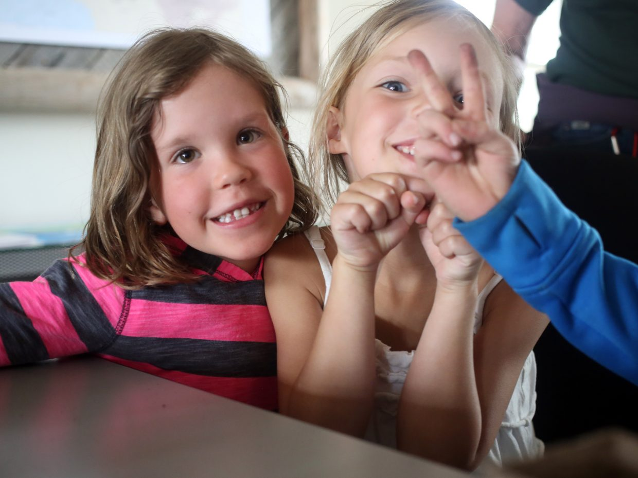 """Molly Grady, right, and Sydney Soard stop for a picture while a classmate attempts to throw up a pair of """"bunny ears"""" Friday at Carpenter Ranch."""