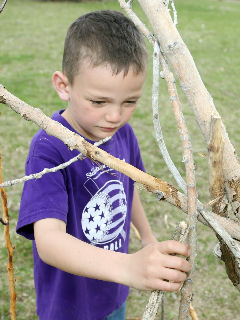 During his lunch break, Hudson Merlina attempts to build a teepee out of sticks at Carpenter Ranch. He got it to stand, but found it eventually fallen over after the day's activities.