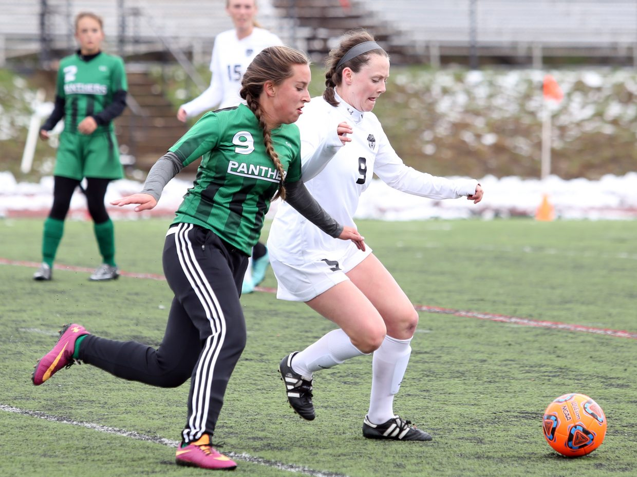 Steamboat Springs senior Jordi Floyd, right, chases down a loose ball alongside Delta's Sierra Baldozier on Saturday at Gardner Field. The Sailors won, 3-0.