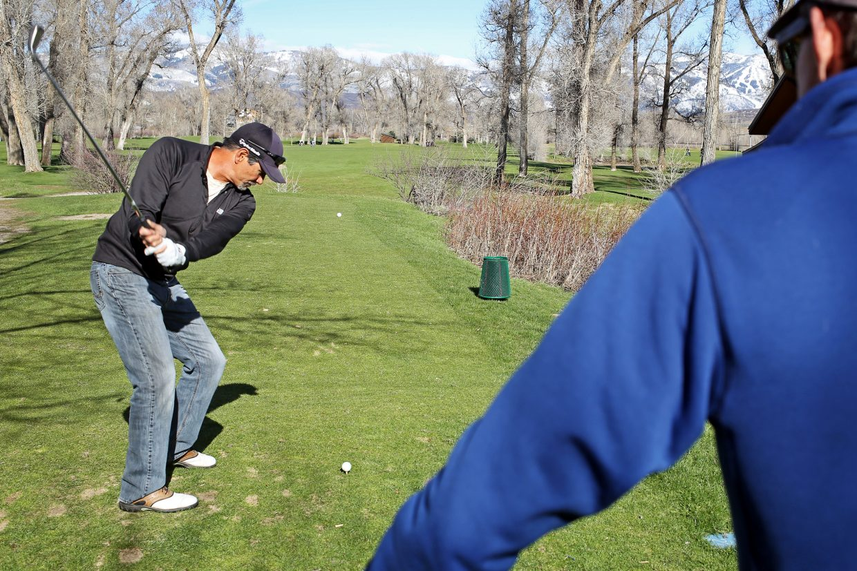 Steamboat Springs resident Dan Foote, right, watches Bob Yokota tee off Sunday at the Steamboat Golf Club. The duo took to the course and enjoyed the first day of May's spring-like weather.