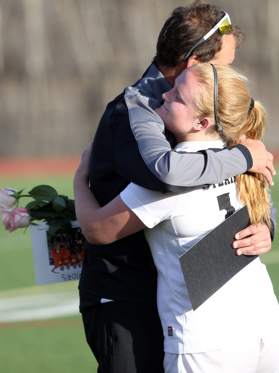 Steamboat senior Tess Richey gives coach Rob Bohlmann a huge during the senior day festivities at halftime.