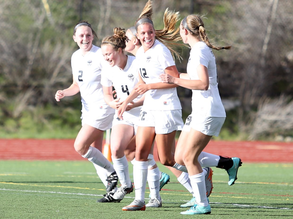 SSHS senior Natalie Bohlmann, No. 12, is surrounded by her teammates after she scored her third goal against Longmont on Wednesday at Gardner Field.