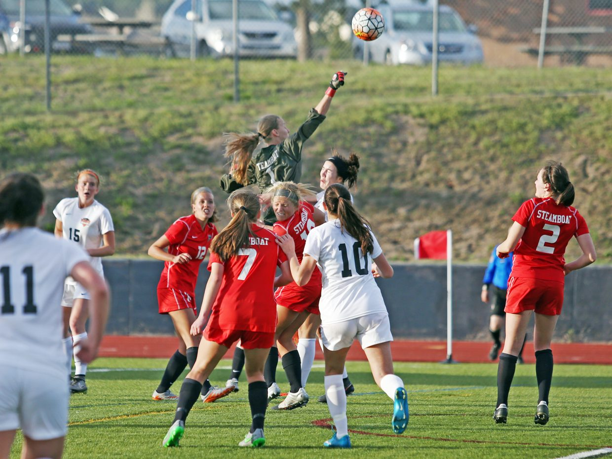 Steamboat Springs senior goalie Ocoee Wilson rises above the crowd to punch away the ball against Lewis-Palmer Thursday in Monument.