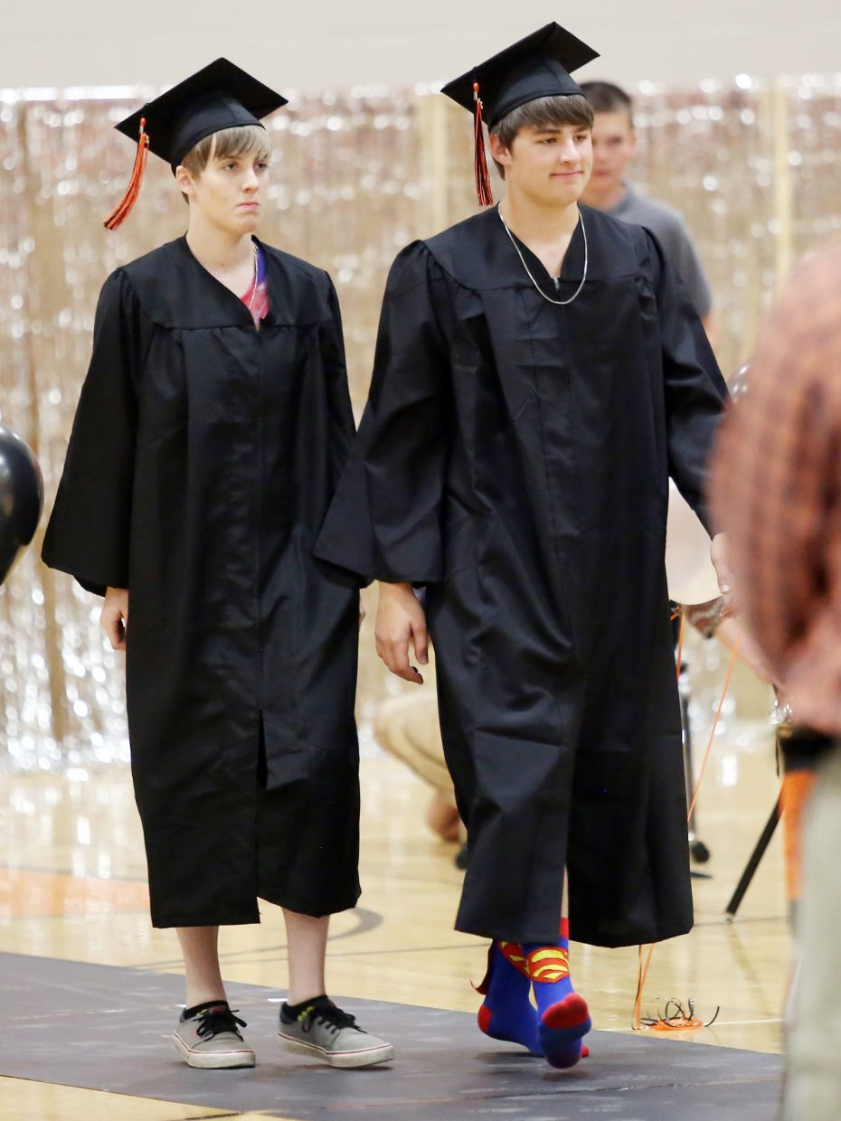 Hayden High School seniors Tyra Camilletti, left, and Garrett Camilletti enter the gymnasium during Sunday's graduation processional.