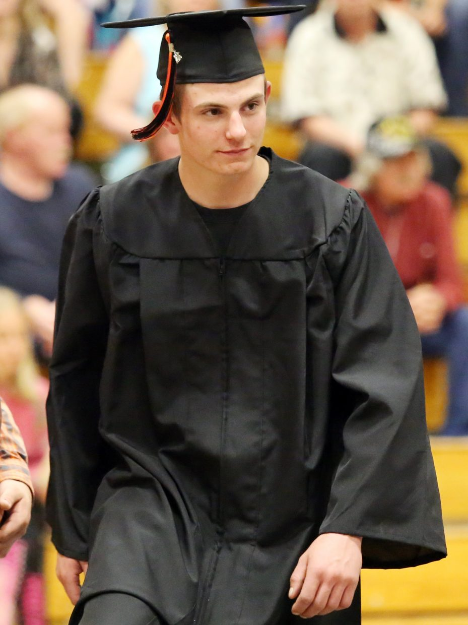 Kenny Corriveau walks across the stage Sunday during graduation at Hayden High School.
