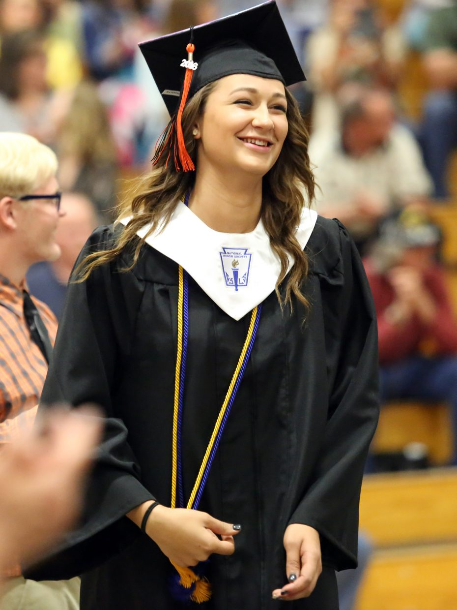 Emma Johnson walks across the stage Sunday during graduation at Hayden High School.