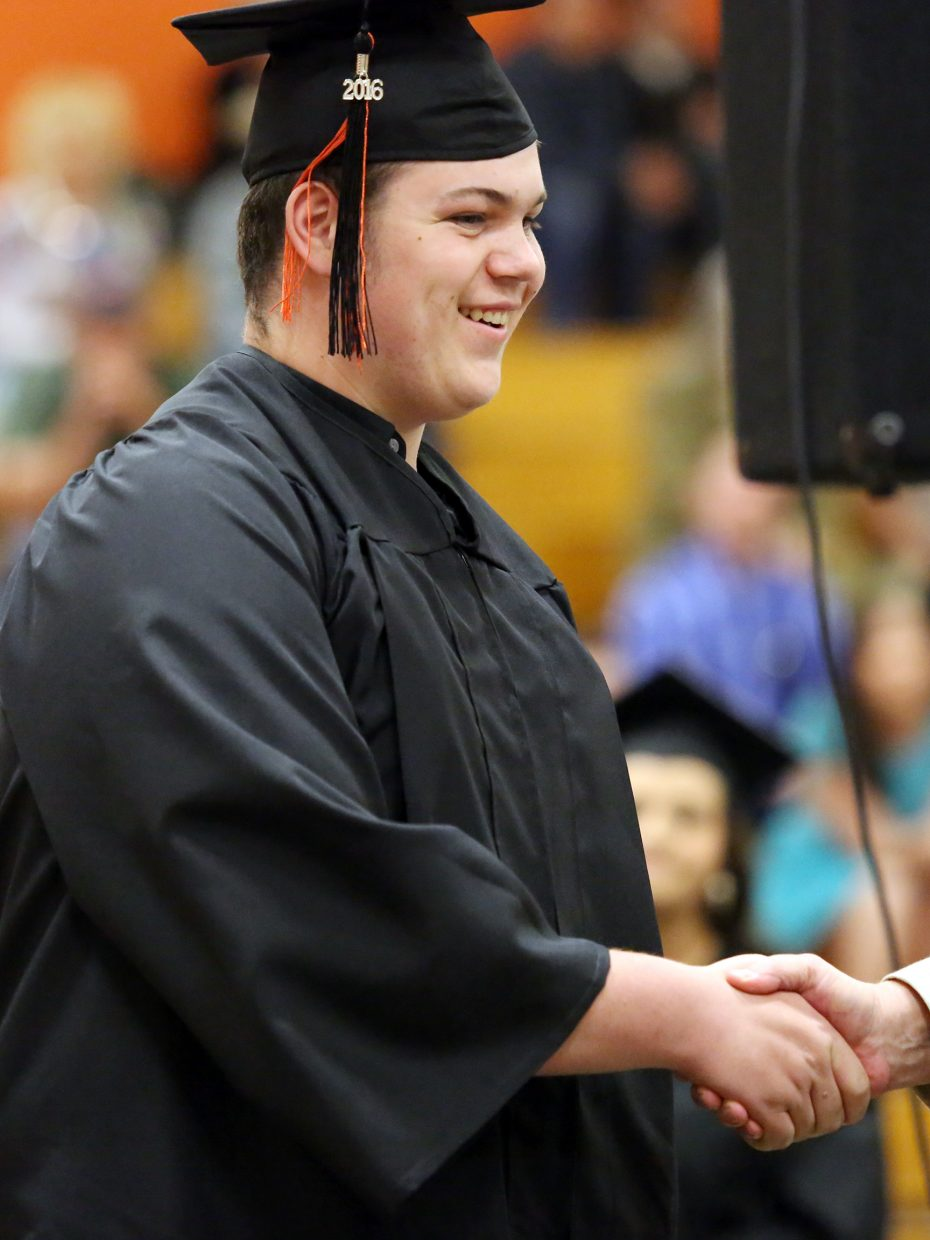 Samuel Newman walks across the stage Sunday during graduation at Hayden High School.