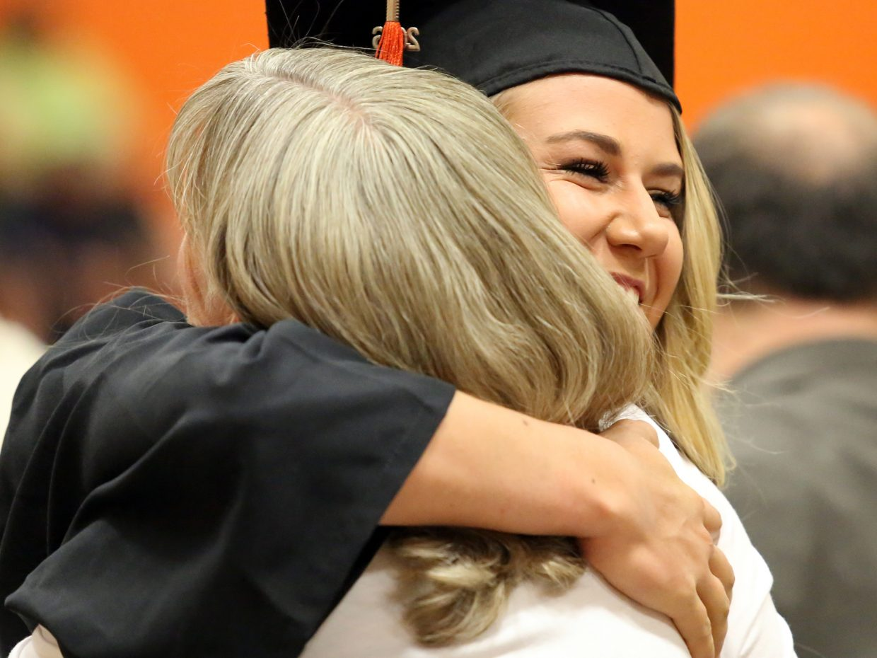 Jewel Vreeman receives a hug after walking across the stage Sunday during graduation at Hayden High School.