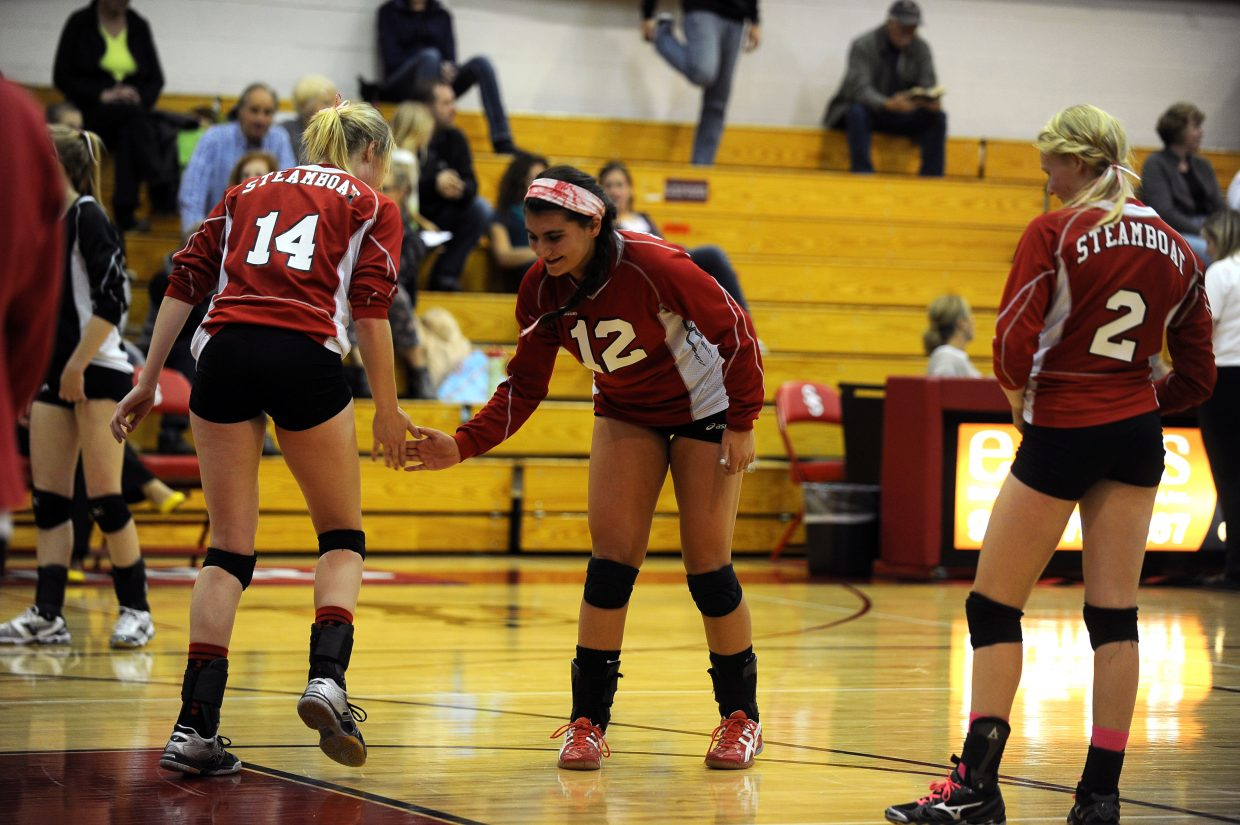 Mikaila Jegtvig (14) and Maddie Labor perform their pre-game handshake before Friday's 3-0 sweep of Palisade.