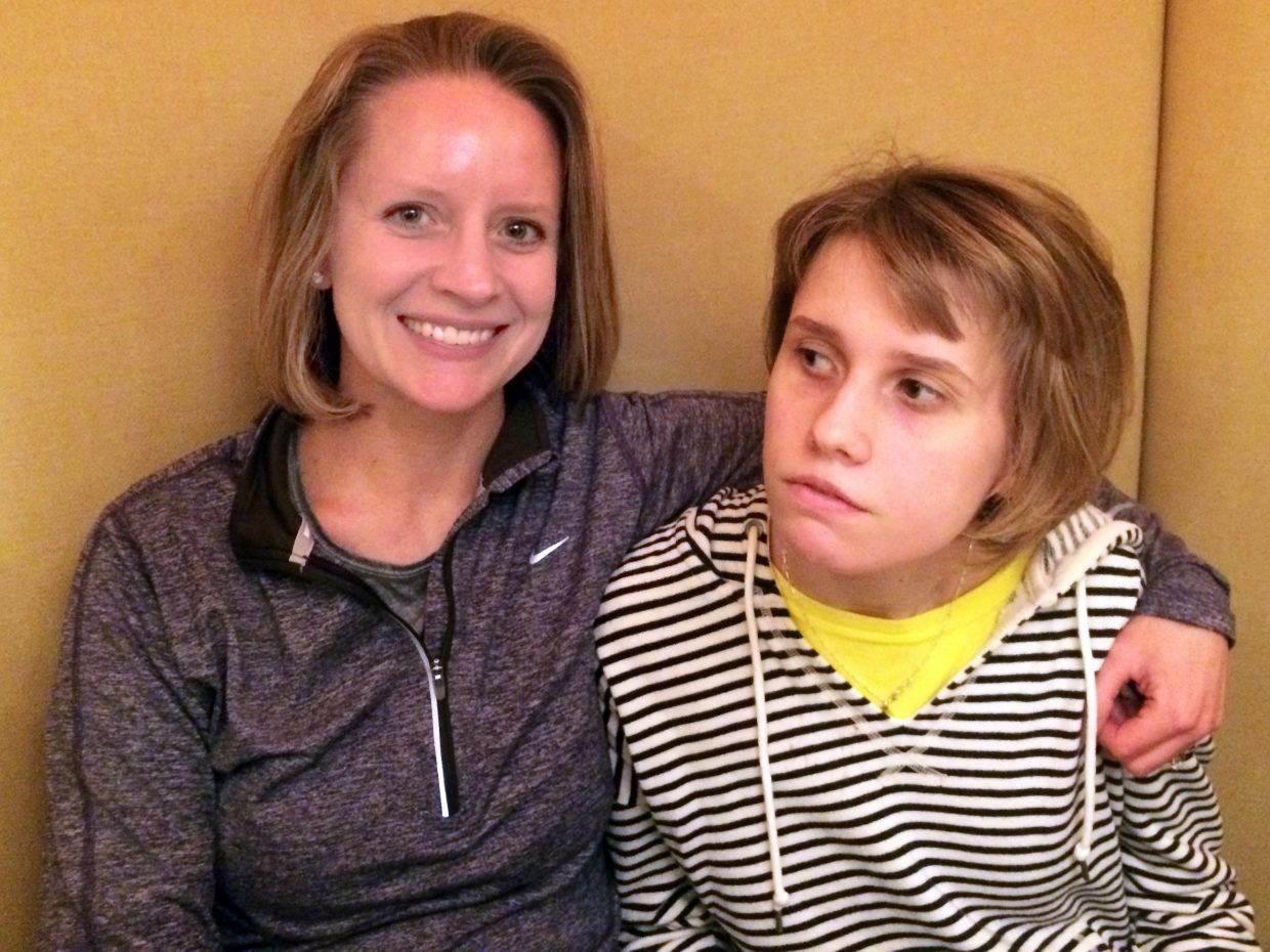 North Carolina's Laura King Edwards, left, sits with her younger sister, Taylor King, who suffers from Batten disease. Edwards will compete in Sunday's Steamboat Springs half marathon, part of her quest to race in all 50 states to raise awareness about the disease. Colorado will be state No. 13 on her list.