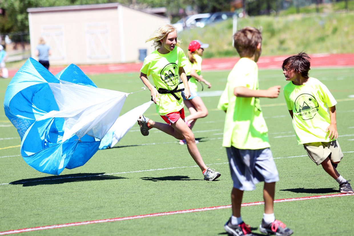 Heidi Andre is dragged down by a parachute during a game of tag, part of Friday's mock meet at the Steamboat Springs Youth Track and Field Camp.