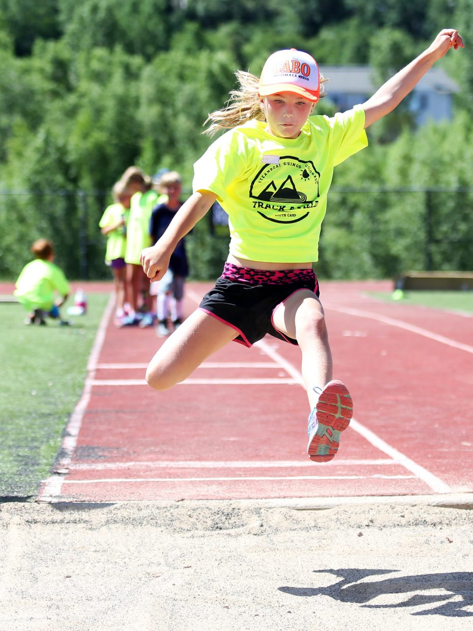 Neve Wade competes in the long jump during Friday's Steamboat Springs youth track and field camp at Gardner Field.