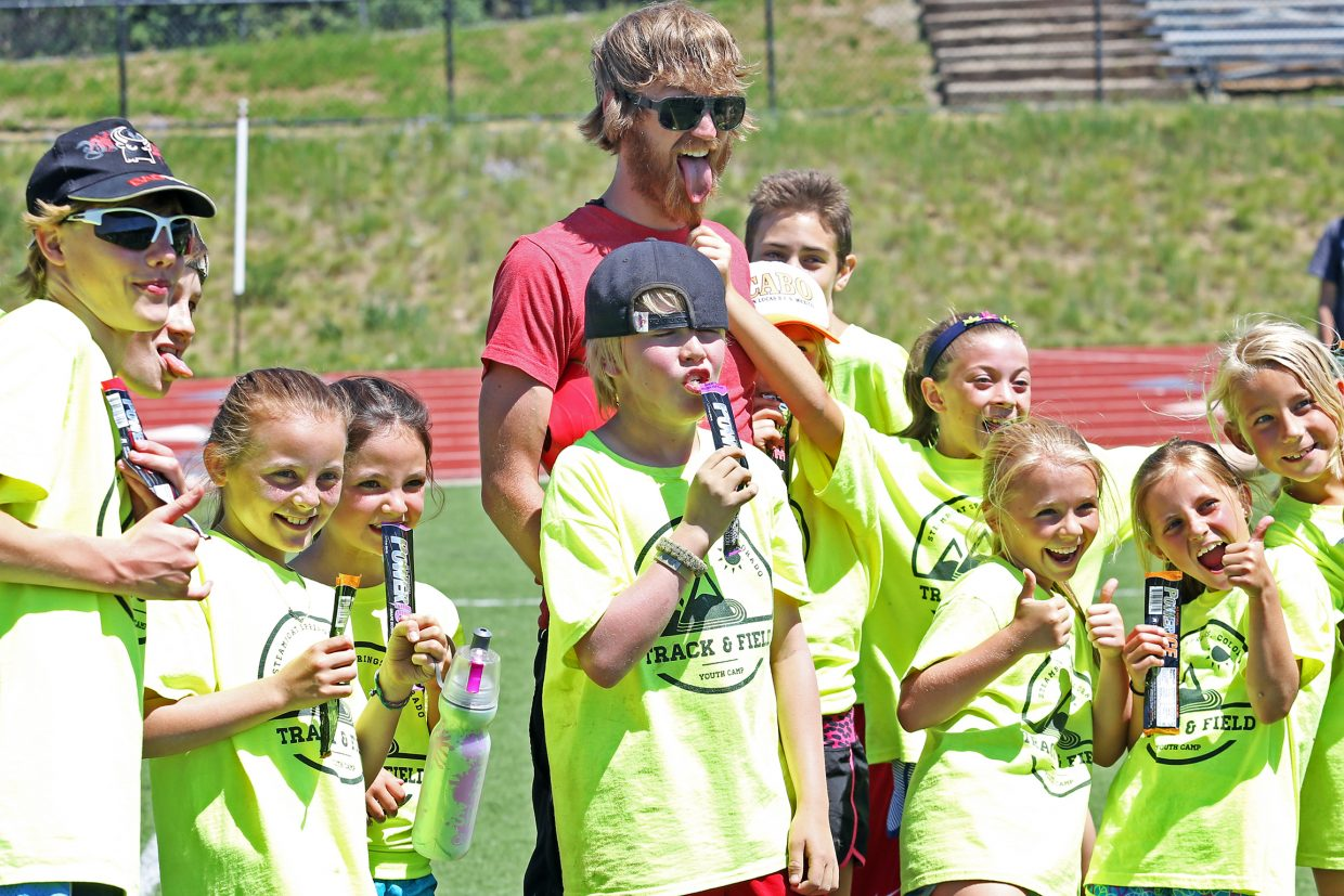 Kids take a picture with coach Erik Ramstad during Friday's Steamboat Springs youth track and field camp at Gardner Field. Ramstad, the former Steamboat Springs High School cross country coach, now lives in Denver but volunteered his time this week to help coach.