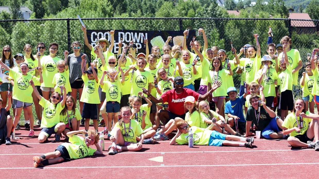 Tony Counts, in red representing PowerICE, takes a group picture with the children that took part in Friday's Steamboat Springs youth track and field camp meet at Gardner Field.