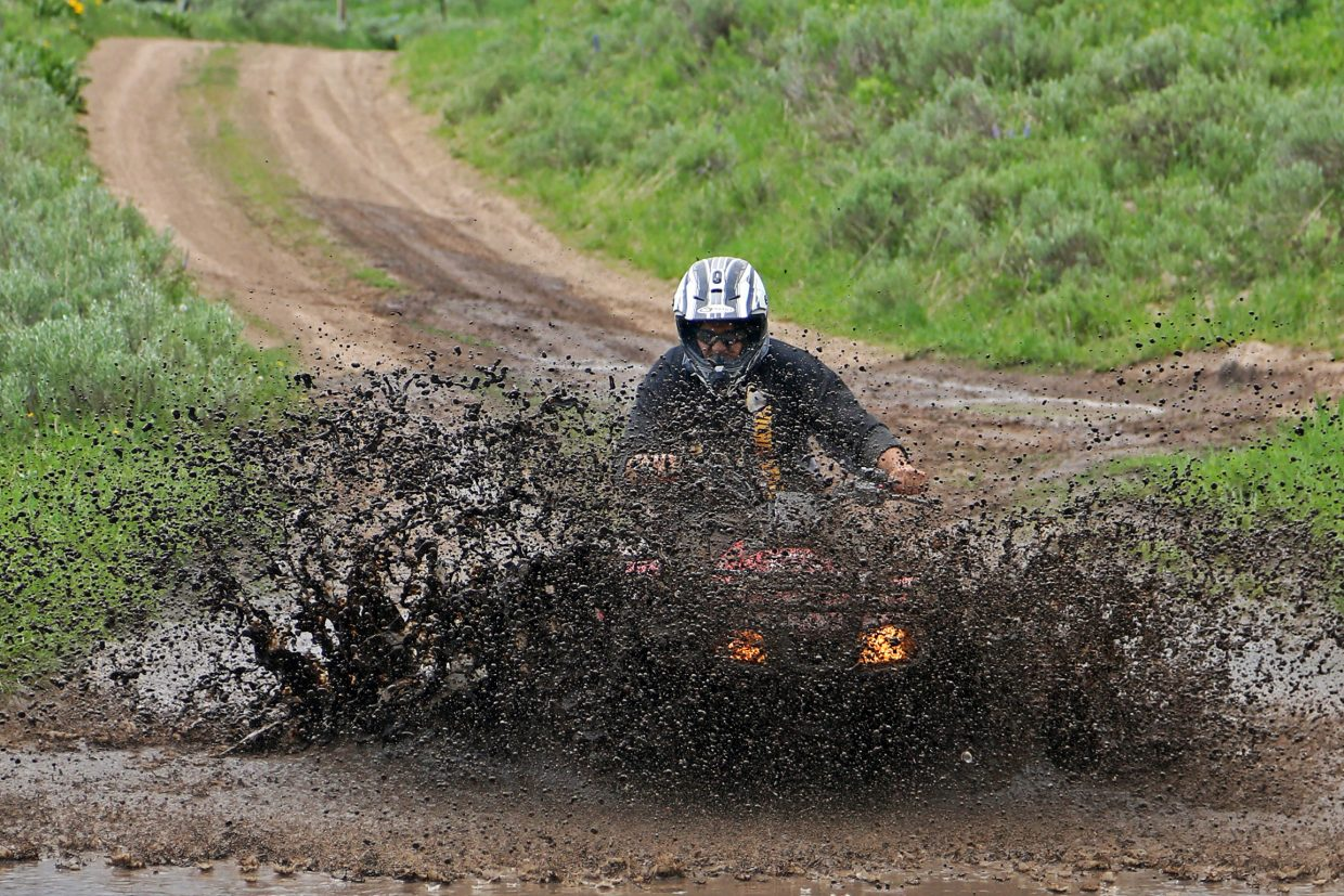 Steamboat Today reporter Austin Colbert finds a mud puddle for his ATV Thursday while on a guided trip with Hahn's Peak Roadhouse in North Routt.