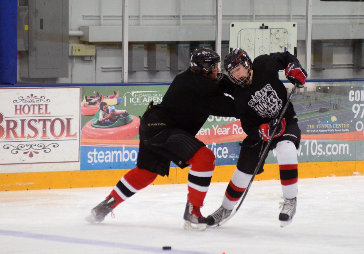 Junior Logan Bankard, left, checks Andrew Firestone during a drill Monday at the Sailors' practice at Howelsen Ice Arena.