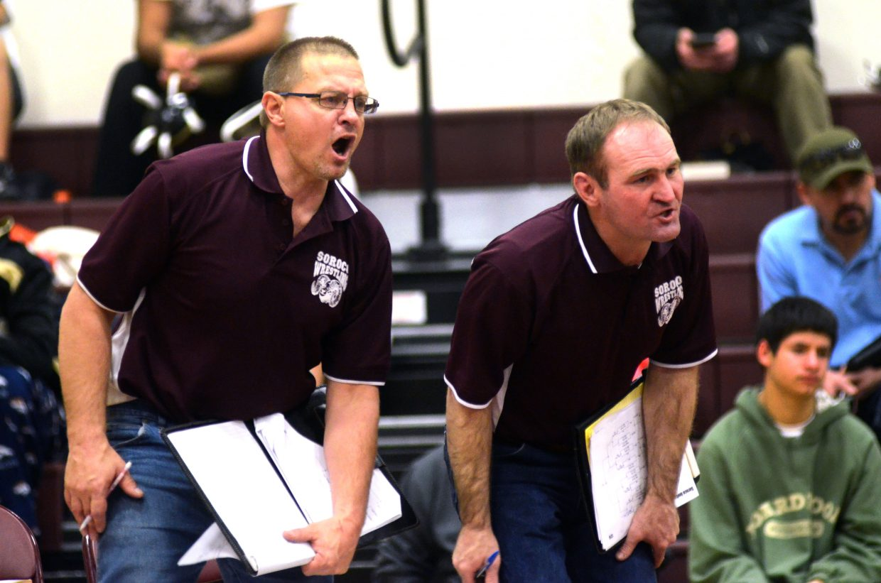 Soroco wrestling coach Jay Whaley, right, and Rams volunteer coach Travis Bruggink shout instructions to Colton Martindale during his 14-2 win over West Grand's Antonio Corrales on Saturday.