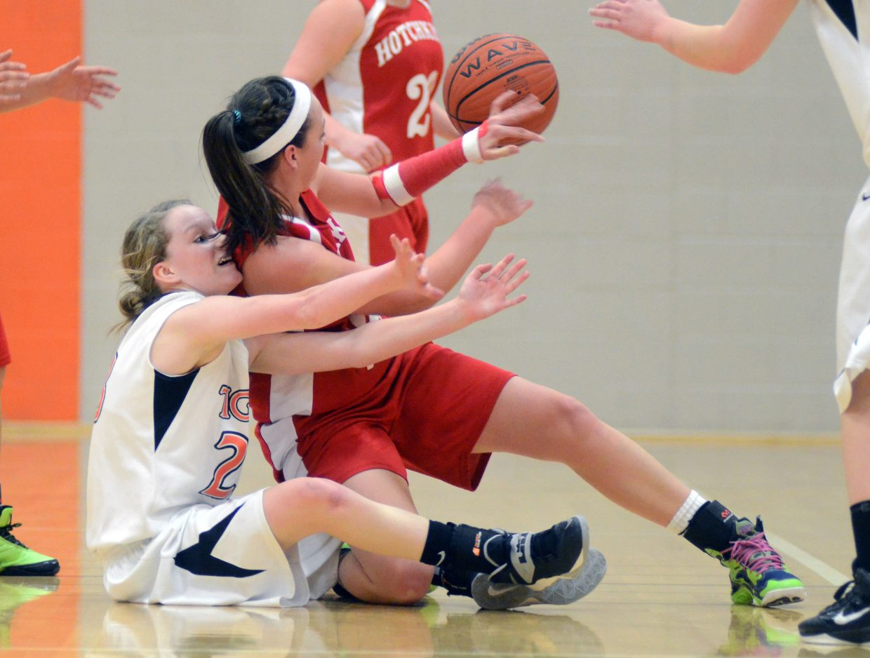 Freshman Grace Wilkie wrestles a Hotchkiss player for a loose ball during the Tigers' 40-point loss Friday night. Wilkie left the game with an injury in the second quarter.