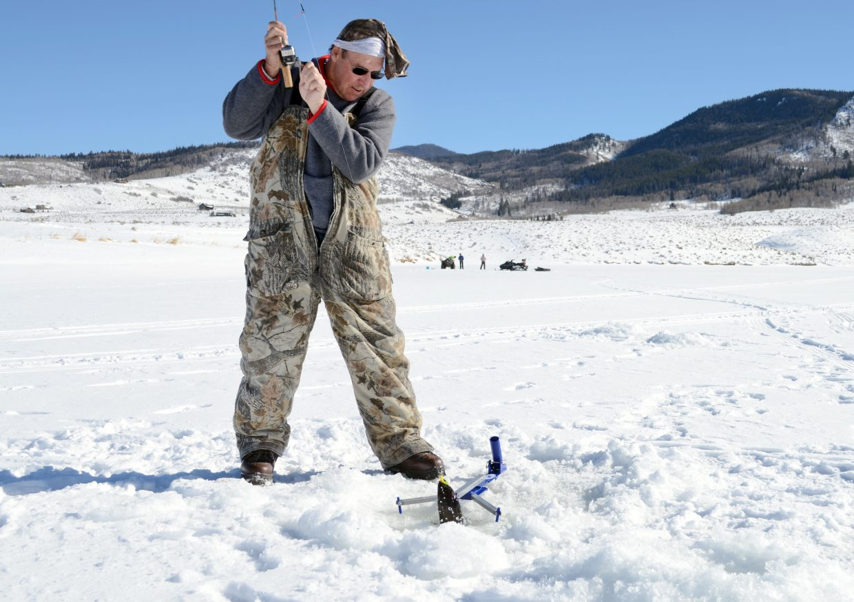 Robin Cook pulls a fish out of the Stagecoach Reservoir waters during Sunday's Steamboat Great Outdoors Ice Fishing Tournament.