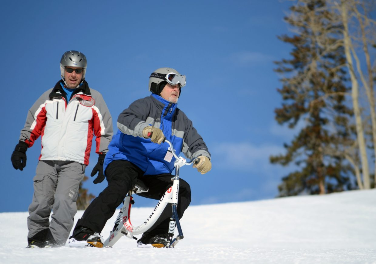 Raymond Sautter, right, gets a snow bike lesson from Steamboat Adaptive Recreational Sports volunteer Randy Wert on Sunday at Steamboat Ski Area. Sautter is a Vietnam veteran.