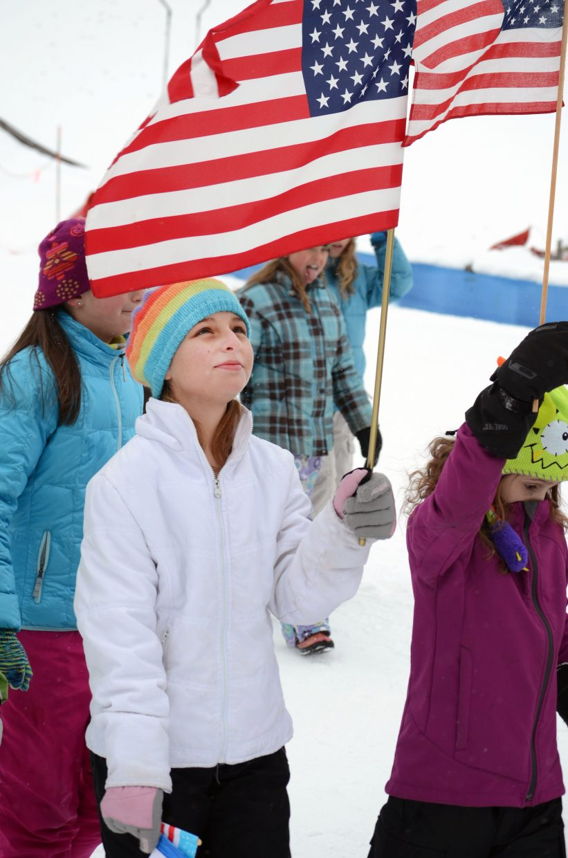 Soda Creek Elementary School student Paula Effinger waves the American flag following the school's version of the Parade of Nations Thursday morning.
