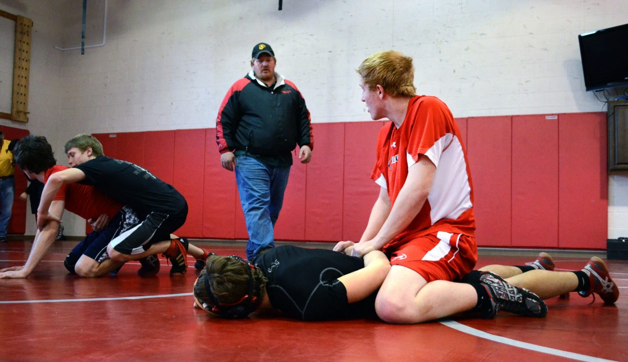 Steamboat Springs High School wrestling coach Shane Yeager, center, gives his son Brandon Yeager instruction during a drill at Tuesday's practice. Brandon is one of three Sailors wrestlers who qualified for this weekend's state tournament in Denver.