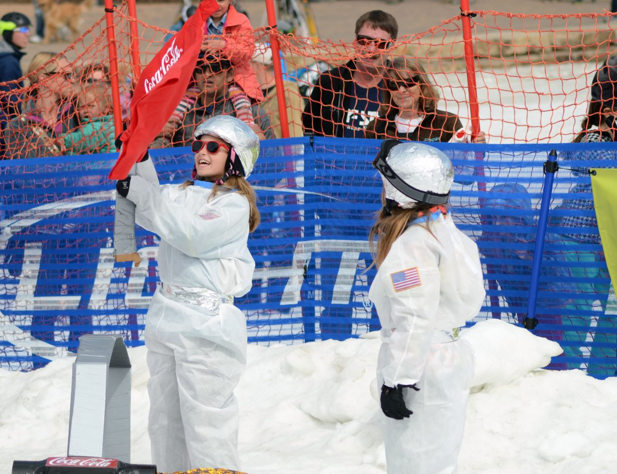 """Gigi Gray, left, waves a victory flag following her """"To Infinity"""" team's win against """"When Pigs Fly"""" at the 34th annual Cardboard Classic on Saturday."""
